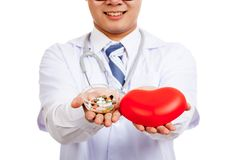 Asian male doctor with red heart and pills Stock Photos
