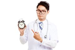 Asian male doctor with serious face  point to a clock Royalty Free Stock Image