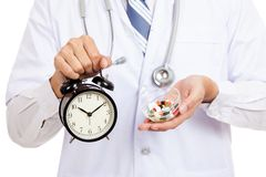 Asian male doctor show a clock and pills Stock Images