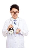 Asian male doctor show a clock and pills Stock Photo