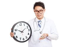 Asian male doctor show a clock and pills Royalty Free Stock Photos