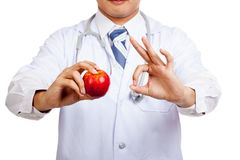 Asian male doctor show OK sign with apple Royalty Free Stock Images