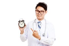 Asian male doctor smile point to a clock Stock Photos