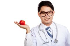 Asian male doctor smile with red apple on palm hand Royalty Free Stock Images