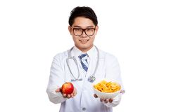Asian male doctor smile with red apple and potato chips Stock Images