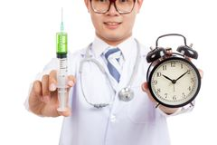 Asian male doctor with syringe and alarm clock Royalty Free Stock Image