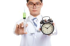 Asian male doctor with syringe and alarm clock Royalty Free Stock Photography