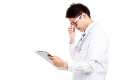 Asian male doctor think  read data on clipboard Royalty Free Stock Photos