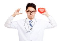 Asian male doctor think with red heart and pill bottle Royalty Free Stock Images