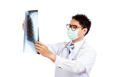 Asian male doctor wear mask look at x-ray film Stock Photography