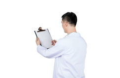 Asian male doctor writing on a medical record chart after medical treatment of patient. Isolated on white royalty free stock photo