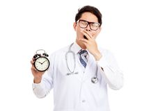 Asian male doctor yawn with a clock Royalty Free Stock Photography