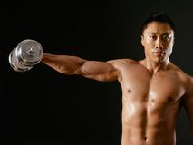 Asian male doing single shoulder fly. Photo of an Asian male exercising with dumbbells and doing shoulder flys or lateral flys over dark background Stock Photography