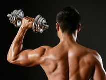 Asian male doing single shoulder press. Photo of an Asian male exercising with dumbbells and doing a single shoulder press over dark background stock image