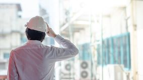 Asian male engineer wearing helmet at construction site royalty free stock photo