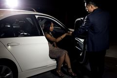 Gentleman Helping Date Out of a Car. Asian male gentleman assisting his black female date out of a car.  The image depicts interracial dating and manners or a Stock Photos