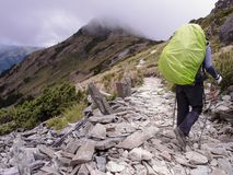 An Asian male hiker carrying a large backpack with fluorescent greens, and walking carefully on a trail with lots of stones.  Stock Image