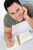 Asian male with his diary. Asian male writing on his diary while lying on the bed Stock Photo