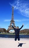 An Asian male jumping in front of Eiffel Tower. An Asian male jumping in joy in front of Eiffel Tower in blue cloths, Parish, France, Europe. Shadow Stock Photo