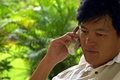 Asian Male Listening Intently On The Phone. An asian male listening on the phone with a concerned look on his face stock photos