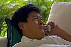Asian Male Listening On The Phone With A Concerned Look. An asian male reclined on a sofa listening intently on the phone with a worried and concerned expression stock photos