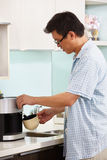 Asian male making coffee Stock Images