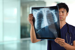 Asian Male nurse looking at X-ray Royalty Free Stock Images