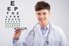 Asian male oculist doing an eyesight test with eye chart Royalty Free Stock Photo