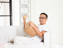 Asian male online shopping with parcel received Royalty Free Stock Image