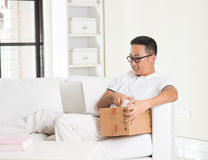 Asian male online shopping with parcel received Royalty Free Stock Photo