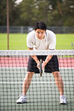 Asian male playing tennis Royalty Free Stock Photos