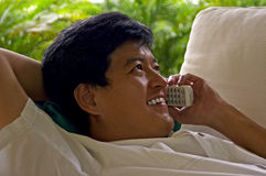 Asian Male Relaxed On The Phone With A Friend. An asian male reclined on a sofa chatting happily on a cordless phone royalty free stock photography