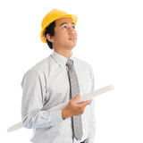 Asian male with safety hardhat. Portrait of attractive Southeast Asian engineer with yellow hard hat and blue prints looking up, standing isolated on white Stock Photos