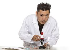 Asian Bio Engineer or Scientist Doing Research. Asian male scientist or microbiologist studying research or experiments with a lab coat and microscope.  He is Stock Photos