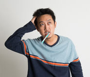 Asian male scratching head and looking up while brushing teeth Royalty Free Stock Photography