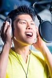 Asian male singer producing song in recording studio. Asian professional musician recording new song or album CD in studio Royalty Free Stock Photo