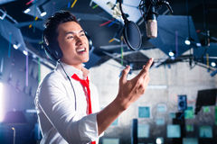 Asian male singer producing song in recording studio. Asian professional musician recording new song or album CD in studio Royalty Free Stock Photography