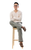 Asian male sitting on a chair Royalty Free Stock Images
