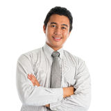 Asian male smiling. Portrait of handsome Asian young man in casual business attire, smiling confidently with arms crossed, standing isolated on white background Royalty Free Stock Photo