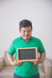 Asian male smiling to camera holding blank chalk board Royalty Free Stock Image