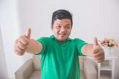 Asian male smiling to camera and showing thumb up Stock Image