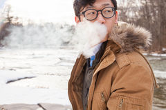 Asian male smoking outside Royalty Free Stock Image