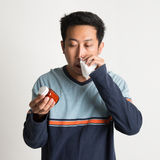 Asian male sneezing Stock Photo