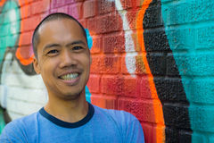 Asian male standing against graffiti wall, smiling Royalty Free Stock Photos