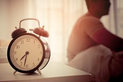 Asian male stretching out after woke up with alarm clock show. Asian male is stretching out after woke up with alarm clock showing six o clock Royalty Free Stock Image