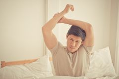Asian male stretching out after woke up on bed. Asian male is stretching out after woke up on bed Royalty Free Stock Images