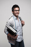 Asian Male Student. Attractive asian male student holding books and bag with a smile Royalty Free Stock Photos