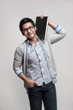 Asian Male Student holding a book on shoulder Royalty Free Stock Image