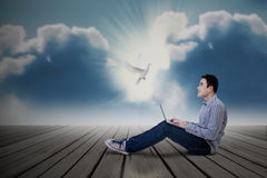 Asian male student looking at dove with laptop Stock Images