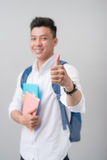 Asian male student making a thumb up sign isolated on white back. Asian male student making a thumb up sign isolated on gray background Stock Photos
